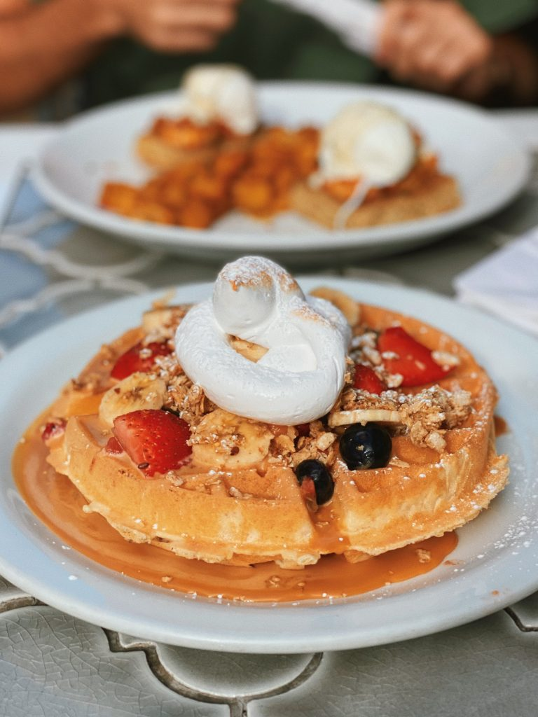 Food picture of a Waffle topped with strawberries, bananas, bluberries and merengue.